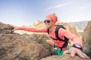 Female runner or climber looking at inspirational landscape on rocky trail on Los Cabos